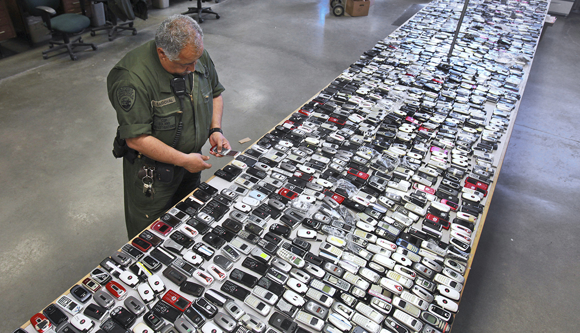 a prison guard inspects a long table entirely covered with contraband cellphones confiscated  from inmates