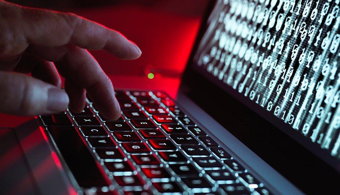 Computadora portátil corriendo un programa malicioso  mientras alguien digita.