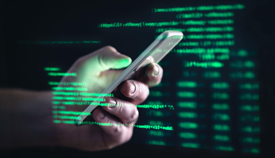 Pantalla con códigos que reflejan una mano con un teléfono móvil.