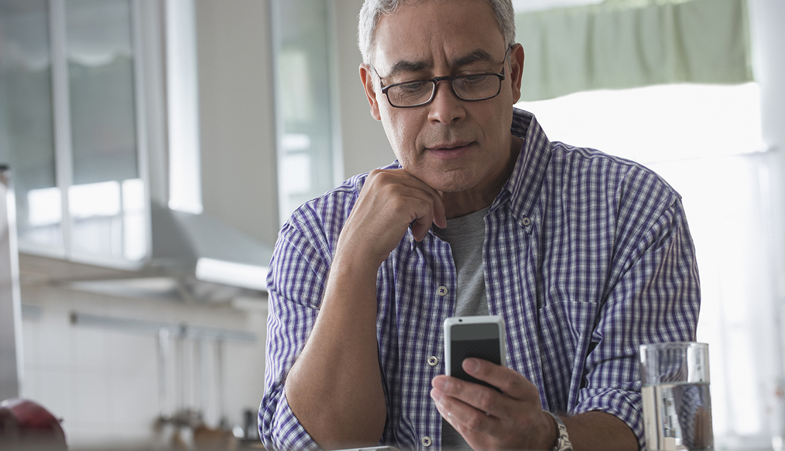 Hispanic man using cell phone in kitchen to read text message