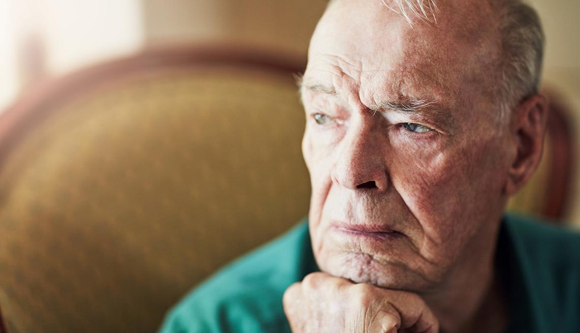 Hombre mayor sosteniendo su cabeza en el puño de su mano.