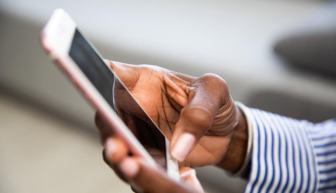 Mano de una mujer sosteniendo un teléfono móvil.