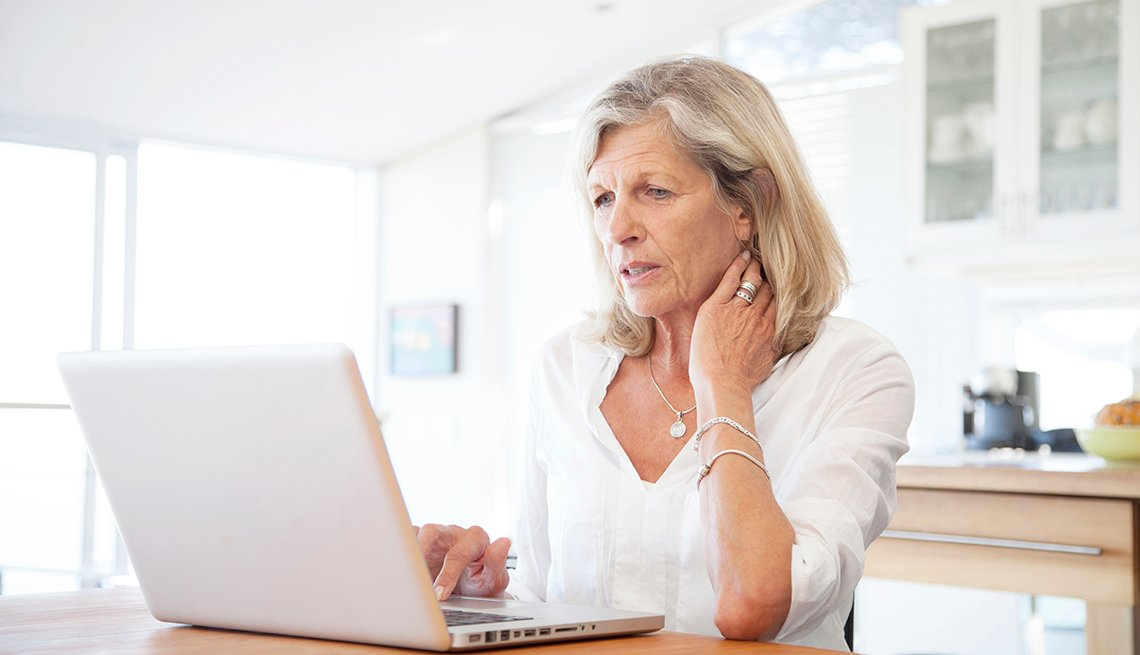 Senior woman, aged 64, working on laptop computer in kitchen