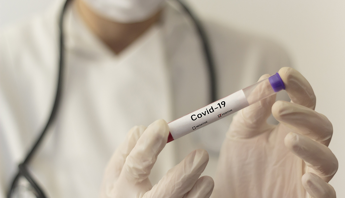 masked and gloved health care worker handing a vial labeled covid 19