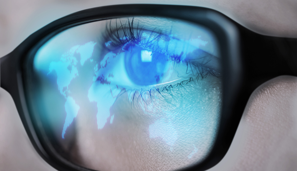 a glowing world map from a computer screen is reflected in a womans eyeglasses