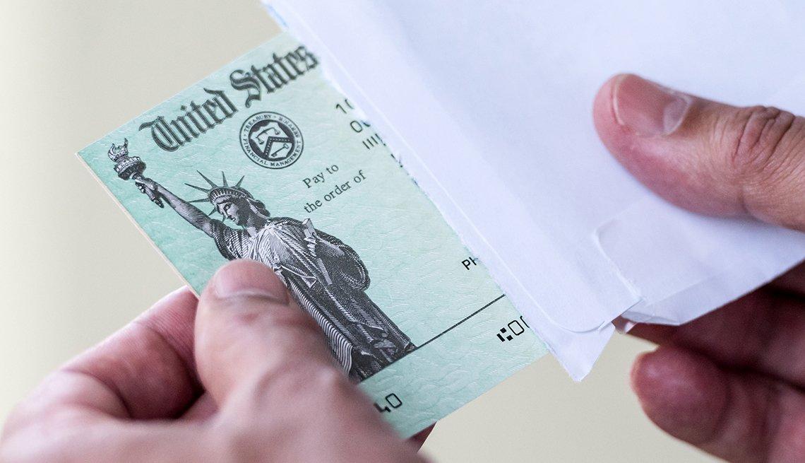 Manos de una persona sacando de un sobre un cheque del Departamento del Tesoro de Estados Unidos.