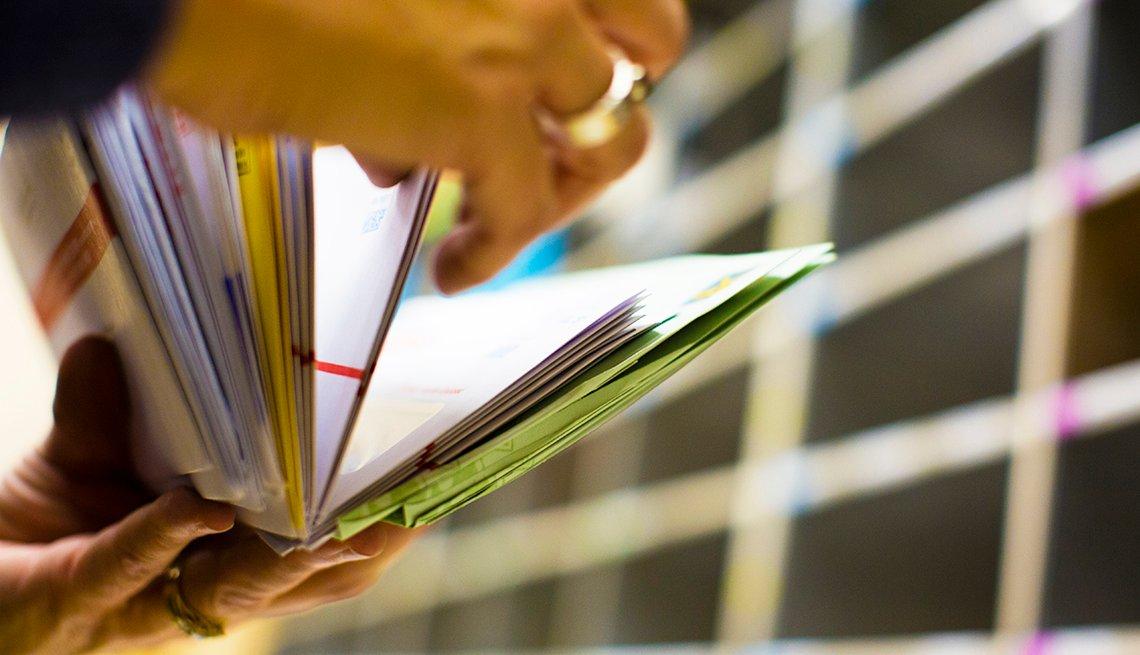 Manos de una persona organizando el correo en una oficina.