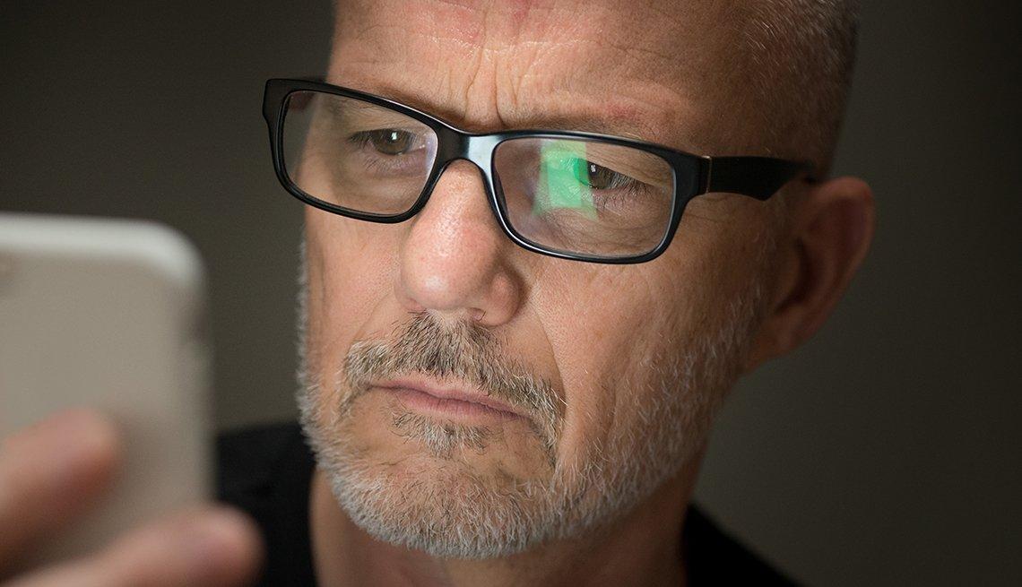 Hombre con lentes sosteniendo un teléfono móvil en su mano y mirando su pantalla.