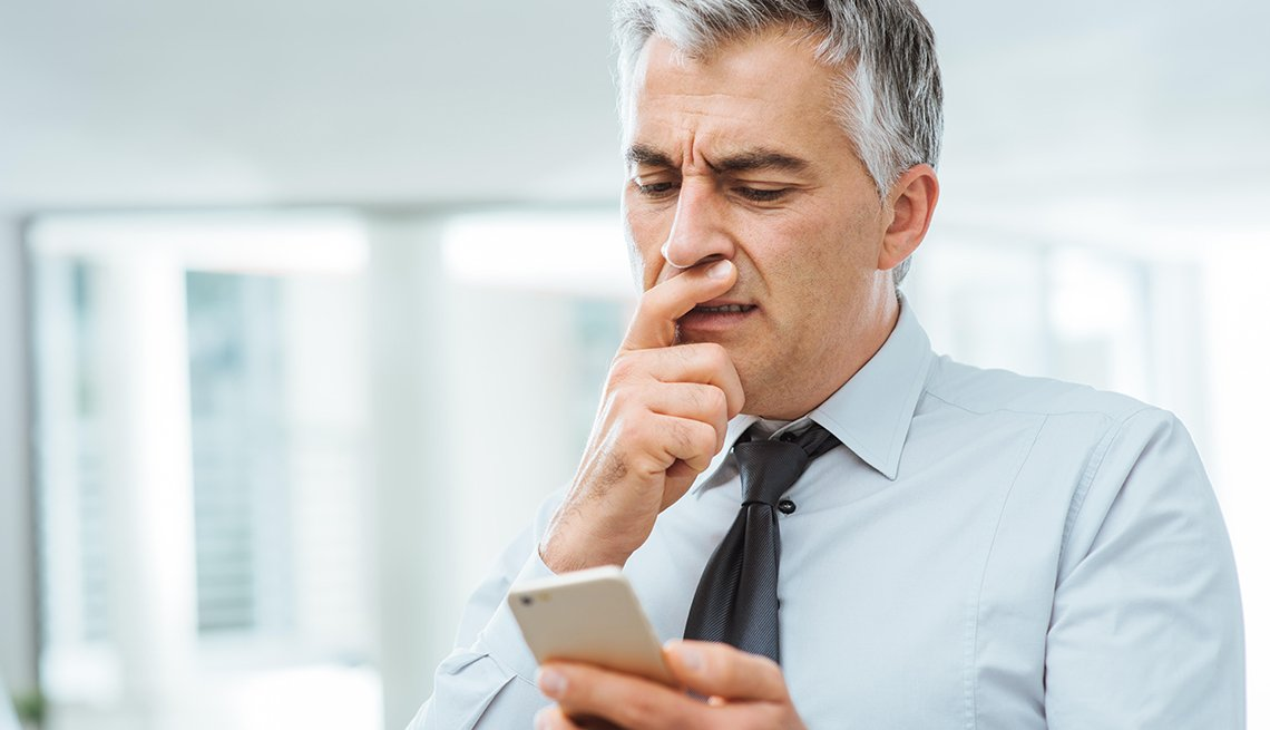Businessman looks questioningly at smartphone