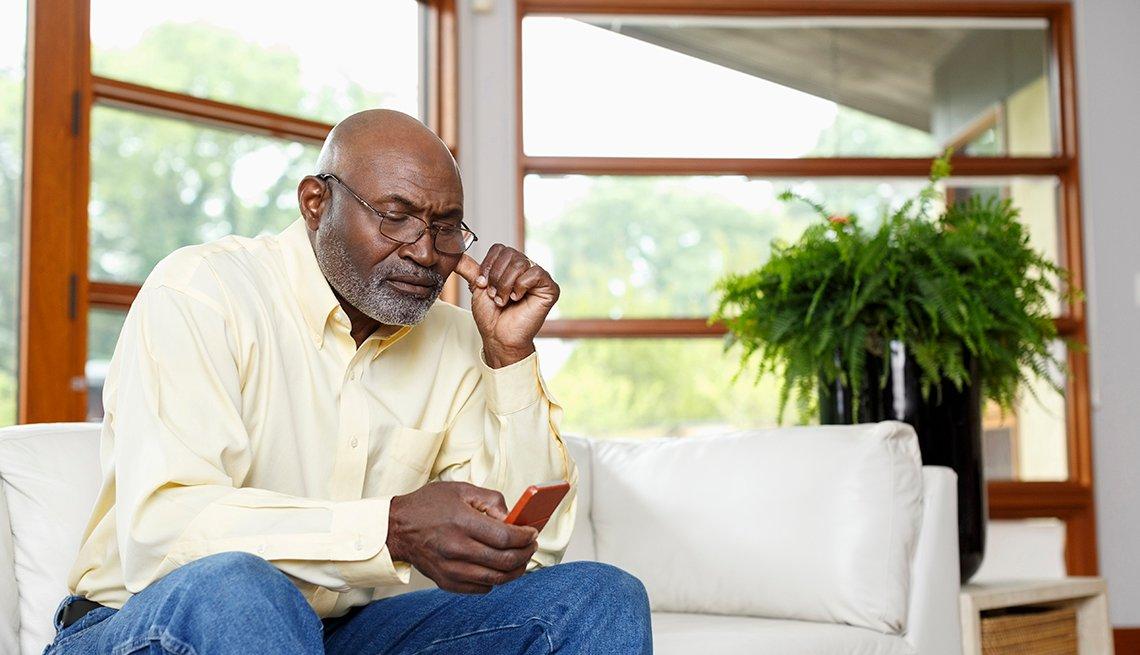 Hombre sentado en un sofá y escribiendo en su teléfono móvil.