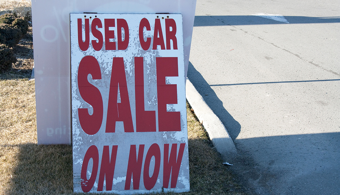 Used car on sale now sign dealership dealer enter road market pavement road