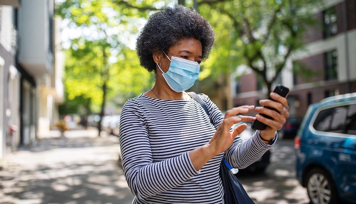 Mujer con una mascarilla en la calle y viendo su teléfono móvil.