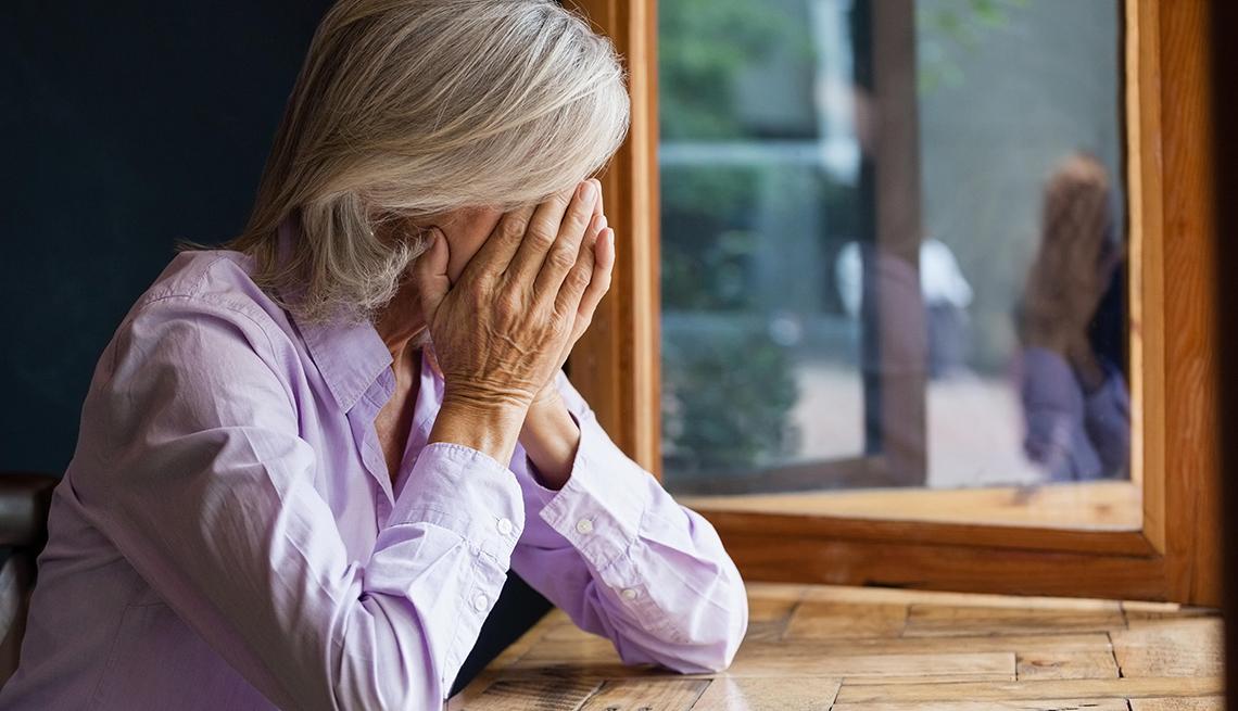 Mujer cubriendo su cara con las manos y apoyada sobre una mesa.