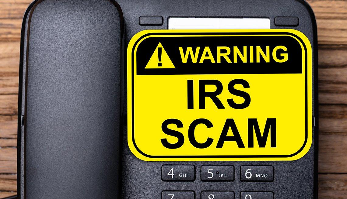 Teléfono fijo con un letrero que dice advertencia fraude del IRS.