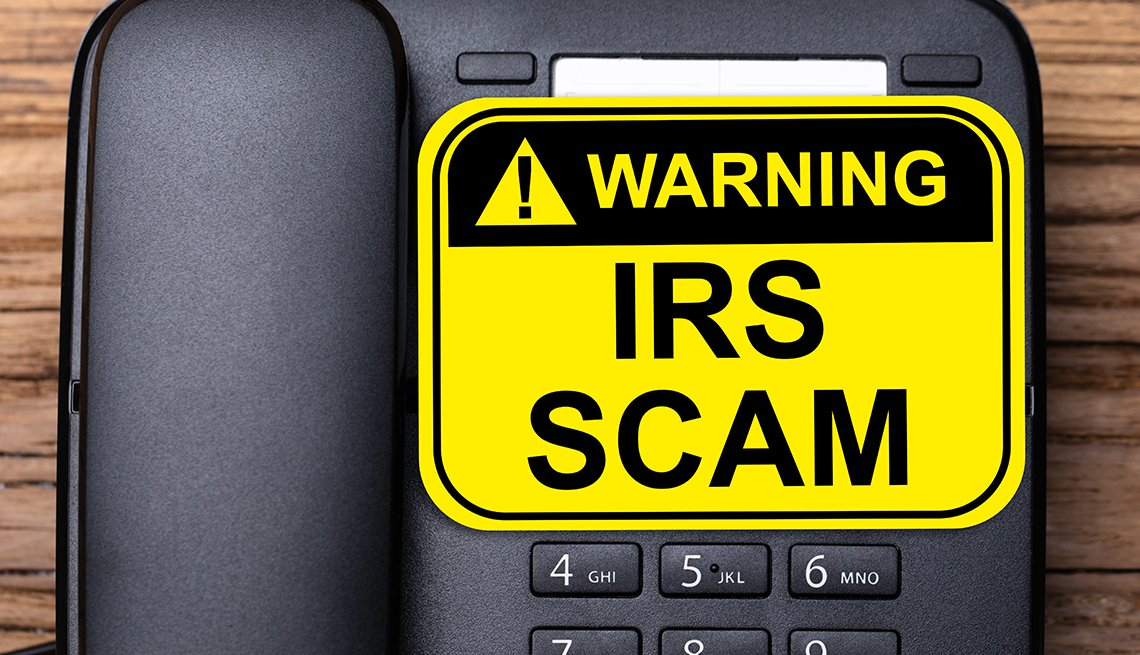 desktop phone with a big yellow warning sticker that says IRS Scam