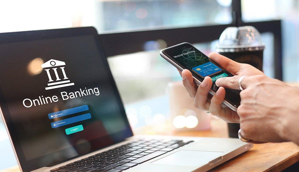Computadora portátil con una pantalla que dice banco en línea encima de una mesa y unas manos que manipulan un teléfono móvil.