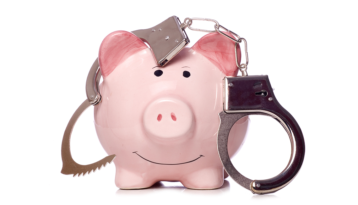 smiling piggy bank draped in a pair of handcuffs against white background