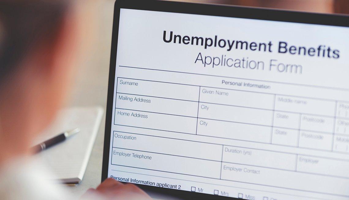 Mujer llenando un formulario de beneficios de desempleo en la computadora.