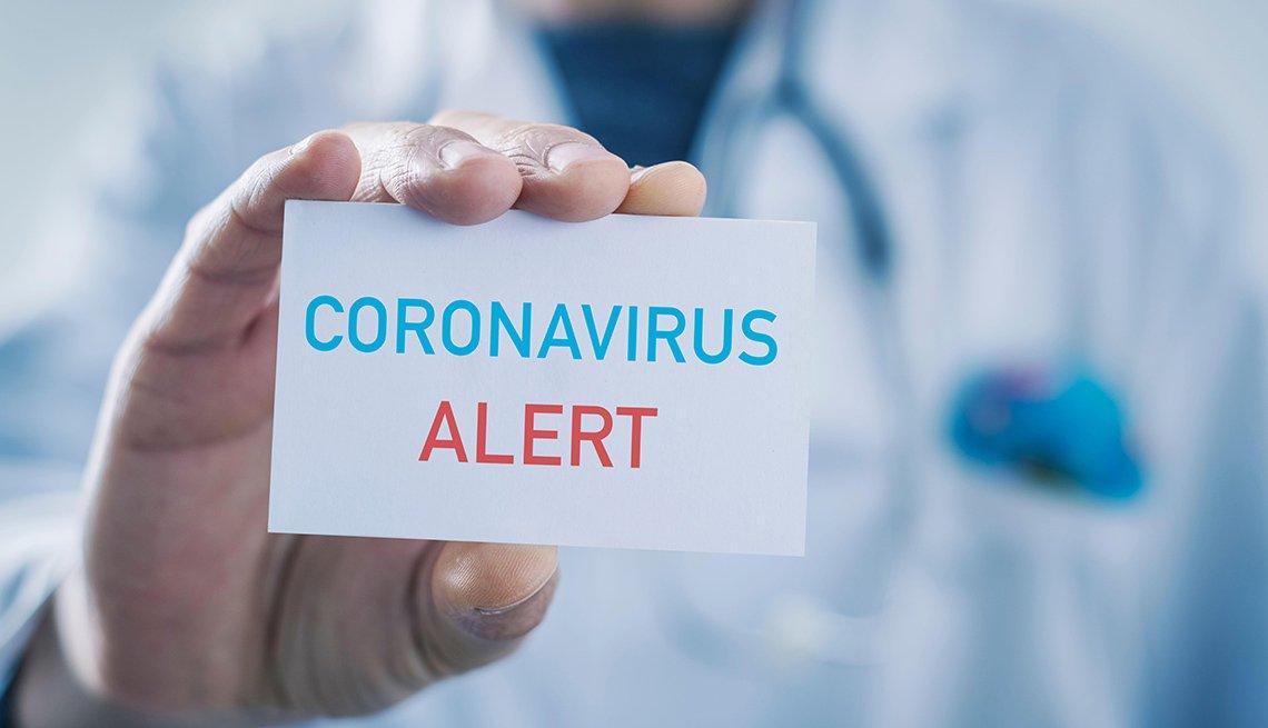 Médico que sostiene una tarjeta que dice alerta de coronavirus.