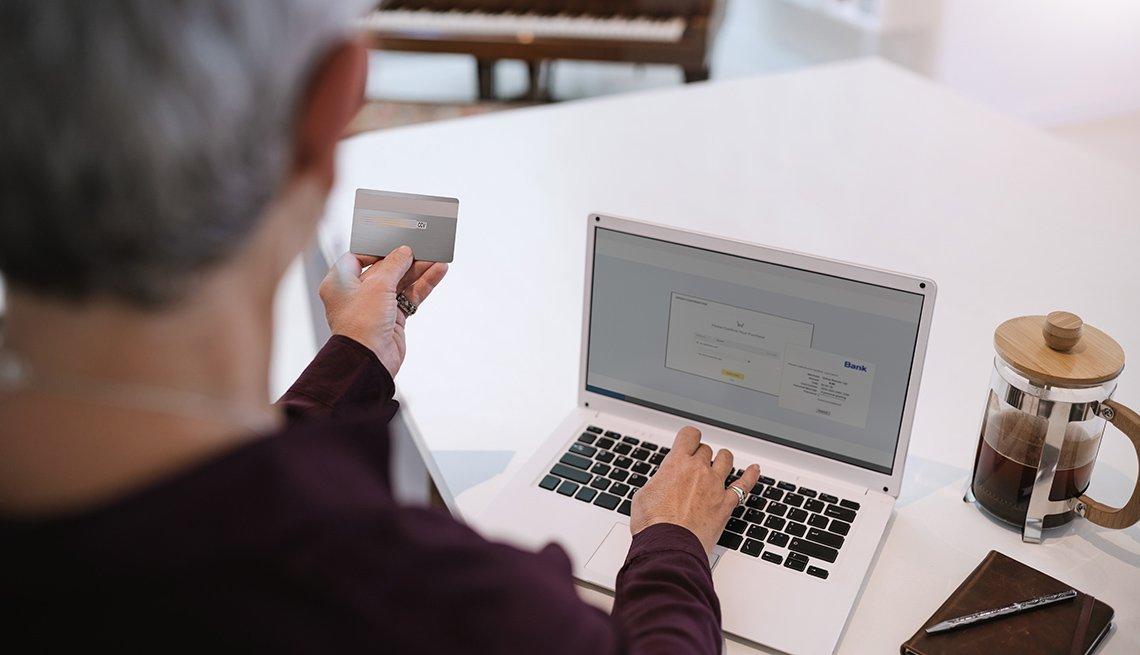 Mujer mayor mirando su tarjeta de crédito y digitando en su computadora personal.
