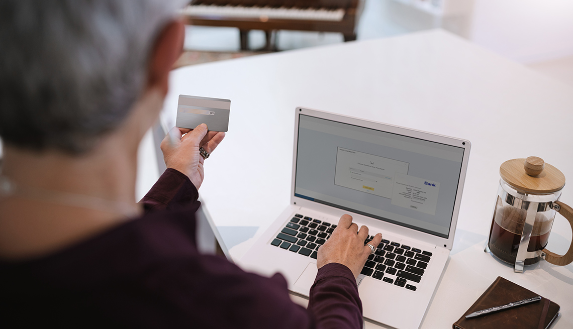 Mature woman shopping online with credit card.