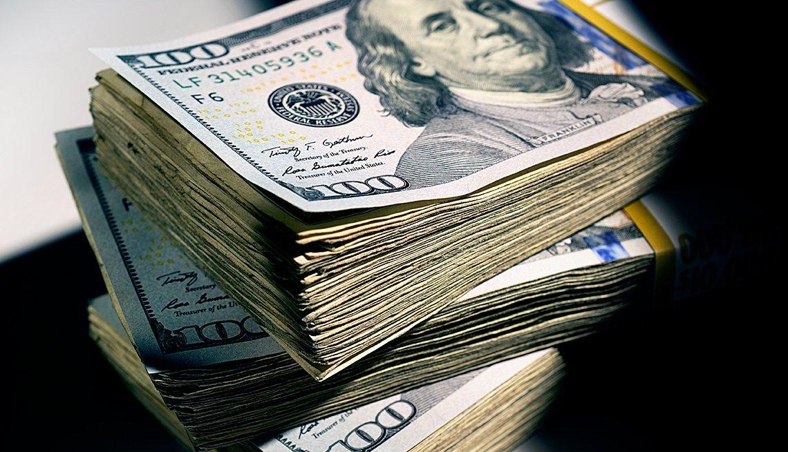 Pila de dinero con billetes de $100.