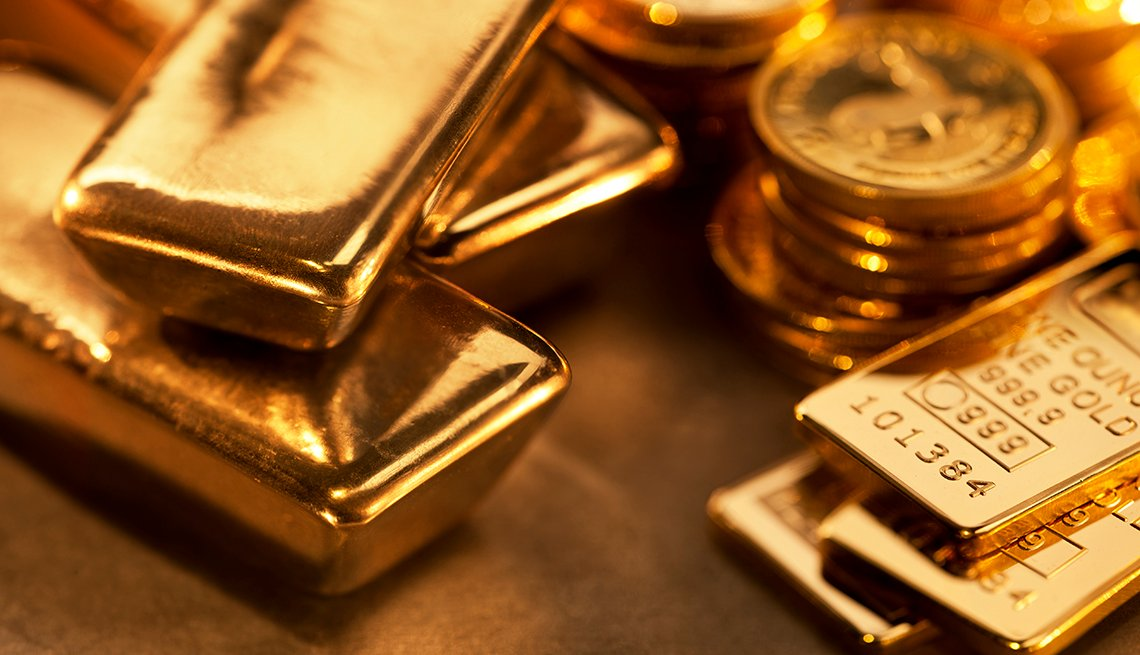 Close up image of assorted gold ingots and gold coins