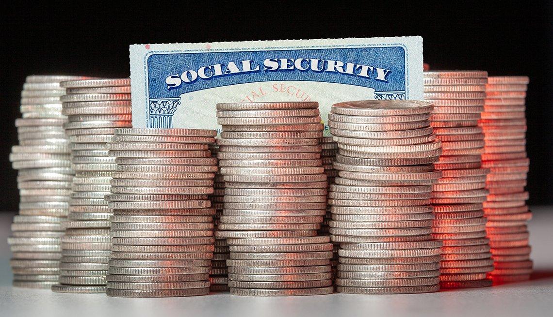 Tarjeta del Seguro Social detrás de varias monedas apiladas.