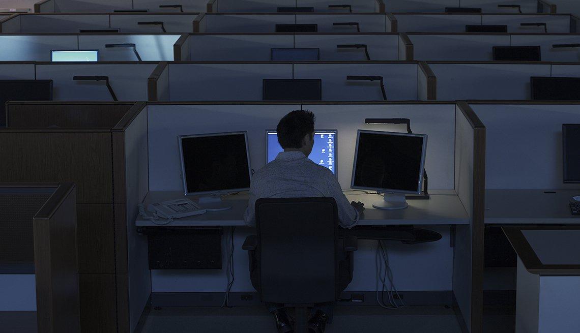 Persona frente a una computadora en un centro de llamadas de servicio al cliente.