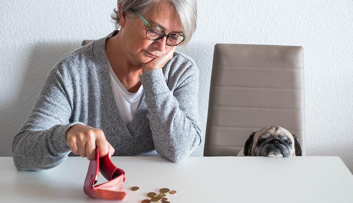 Mujer mirando unas monedas que vacía sobre una mesa.