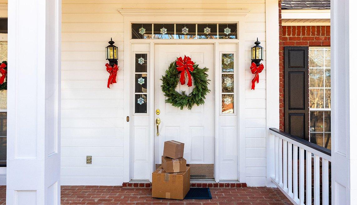 Paquetes frente a una puerta con decoraciones de navidad.
