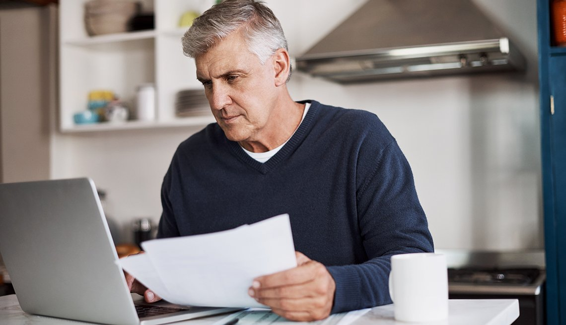 Man reviewing paperwork in kitchen on his laptop