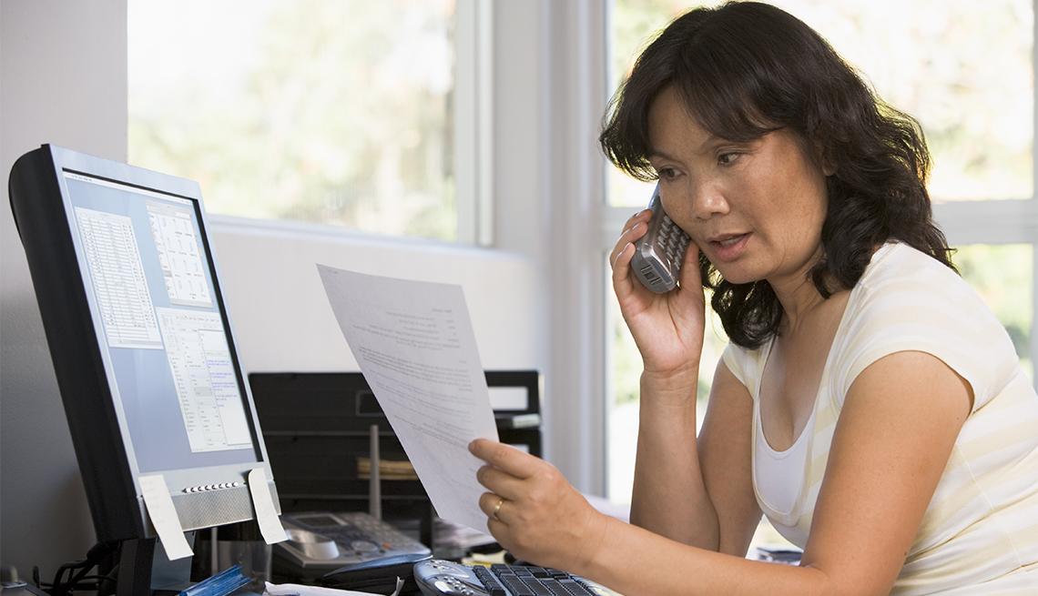 Mujer hablando por teléfono mientras revisa un documento y está sentada frente a la computadora.