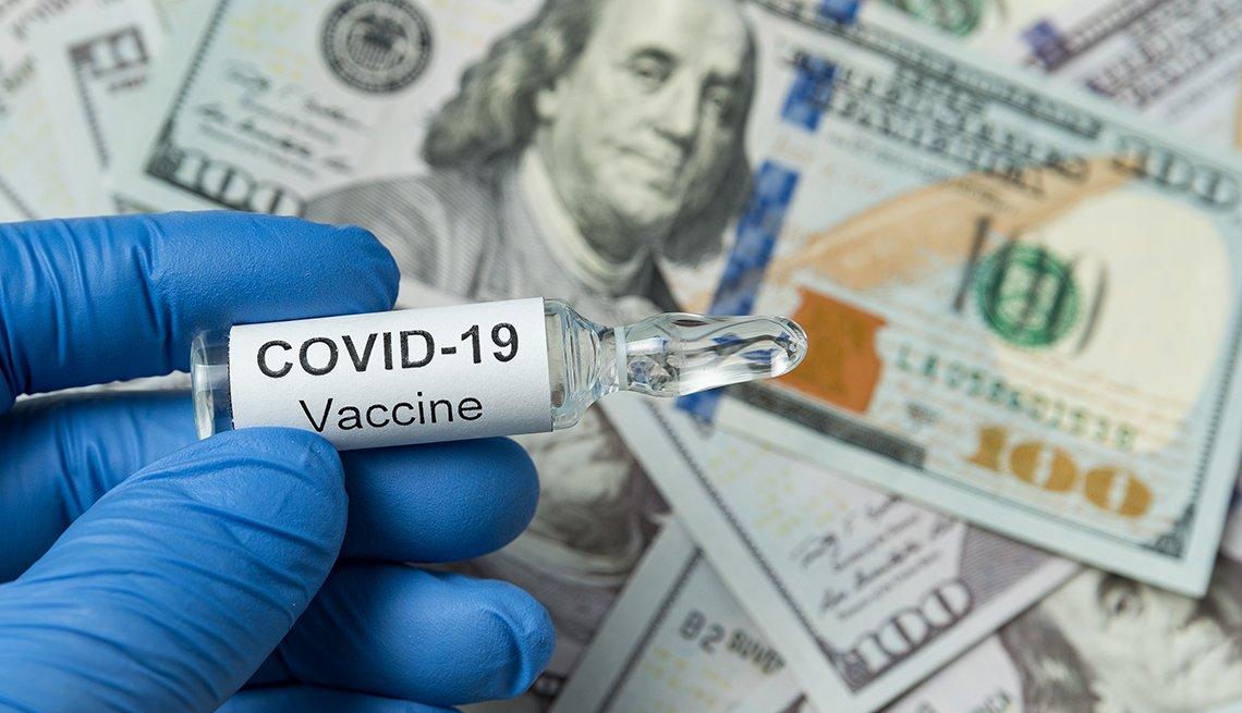 Mano con un guante sostiene una vacuna contra la Covid-19 y al fondo billetes de 100 dólares