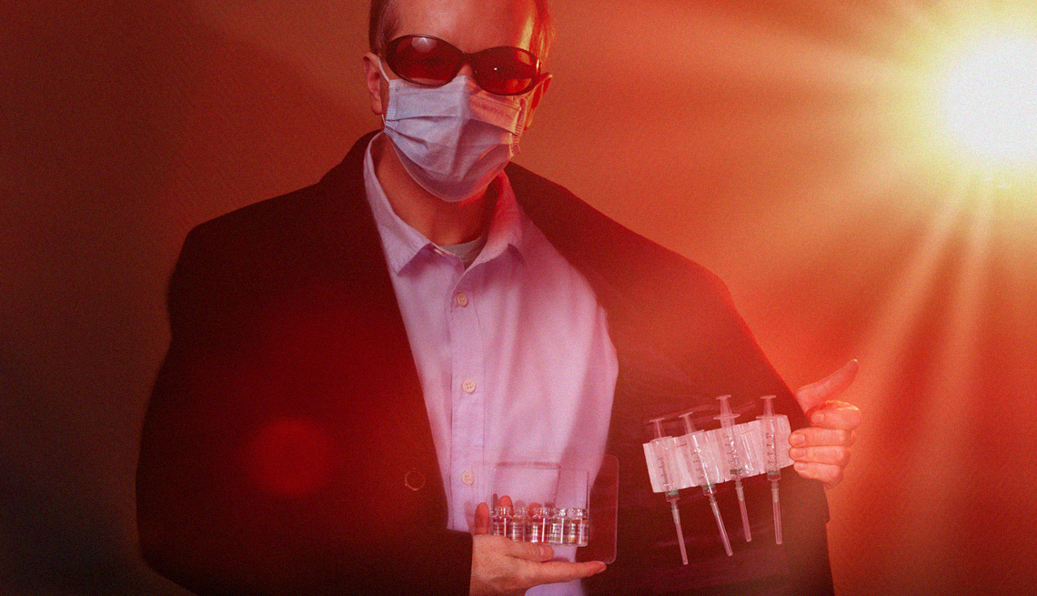 staged photo of a man wearing sunglasses a mask and a coat shiftily showing us his stash of vaccine vials for sale