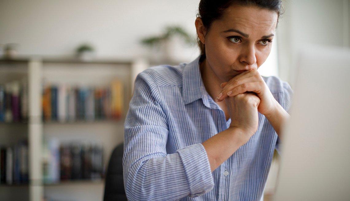 Mujer con las manos en la quijada y con expresión de preocupación mientras mira una computadora.