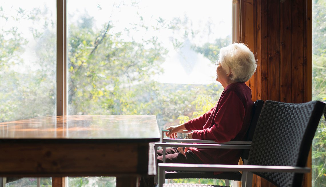 Older woman looking sad out the window