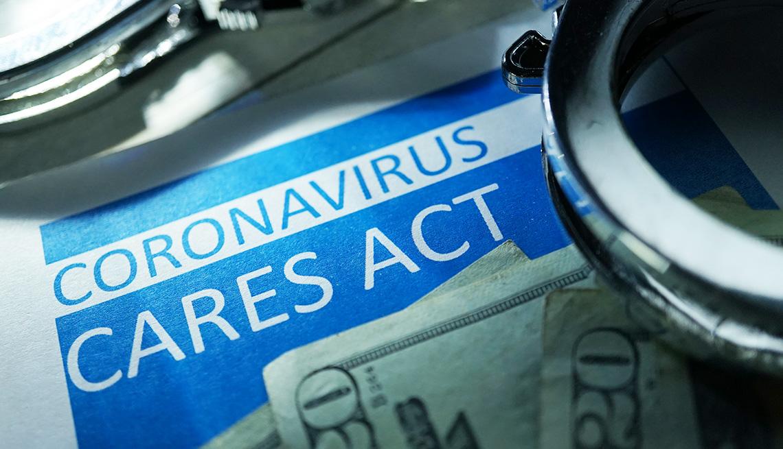 Palabras Ley Cares del coronavirus al lado de un billete de $20 dólares y unas esposas al lado.
