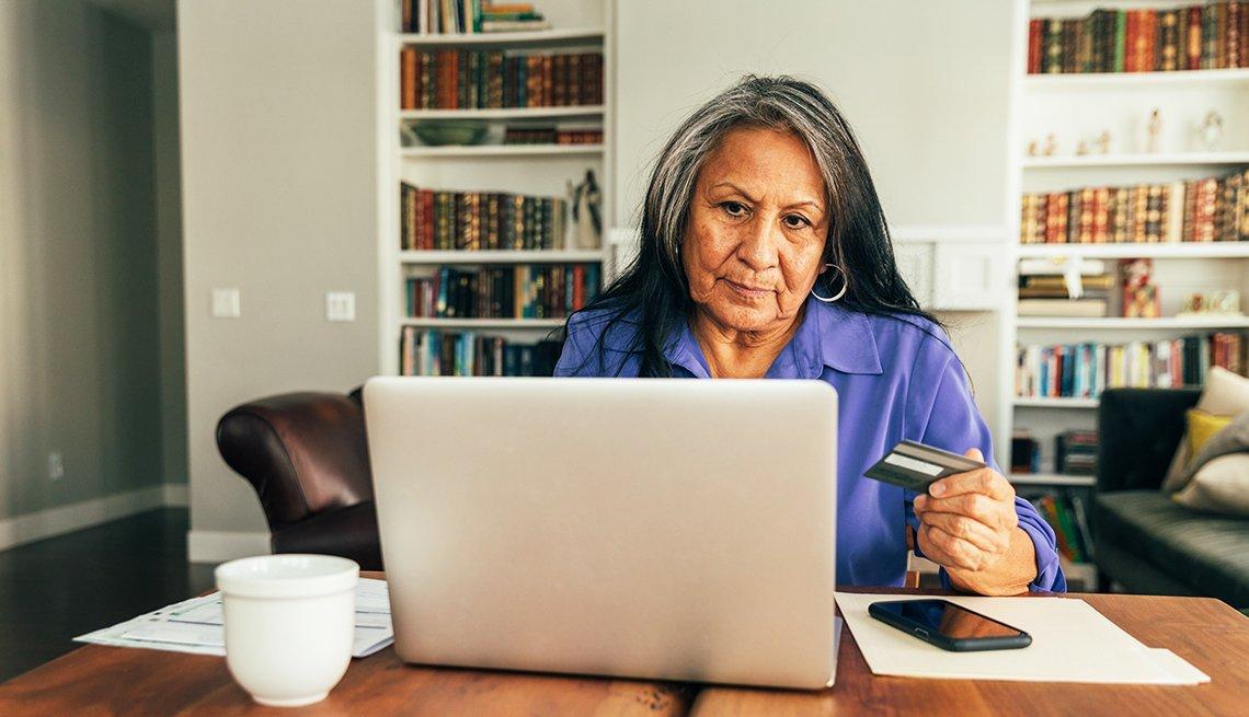 Mujer mayor frente a su computadora en el comedor de su casa.
