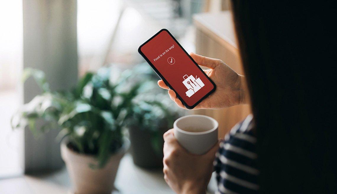 Mujer usando una aplicación en su teléfono móvil mientras en la otra mano sostiene una taza.