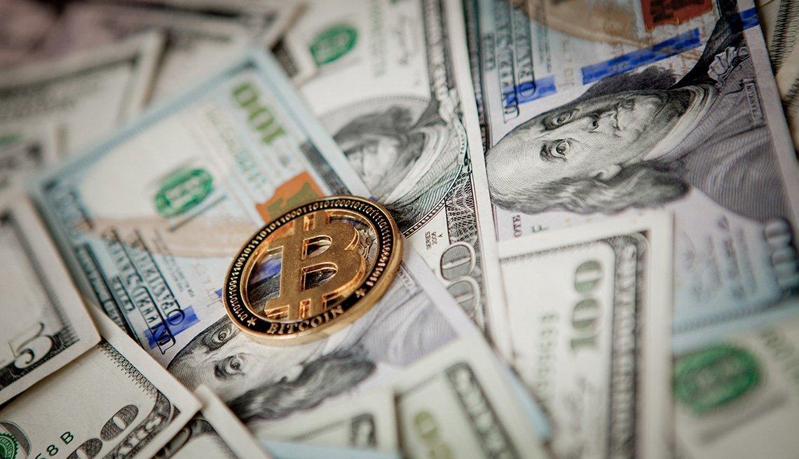 Billetes de $100 dólares con una moneda de oro de bitcoin encima