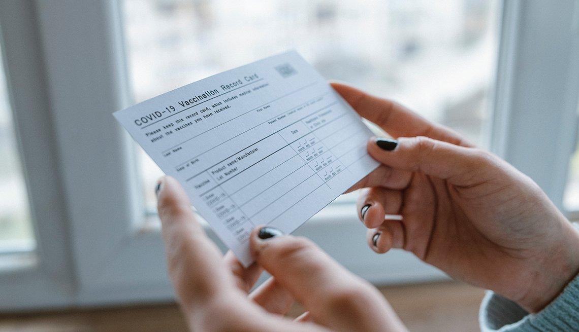 Manos sostienen una tarjeta de vacunación contra la Covid-19