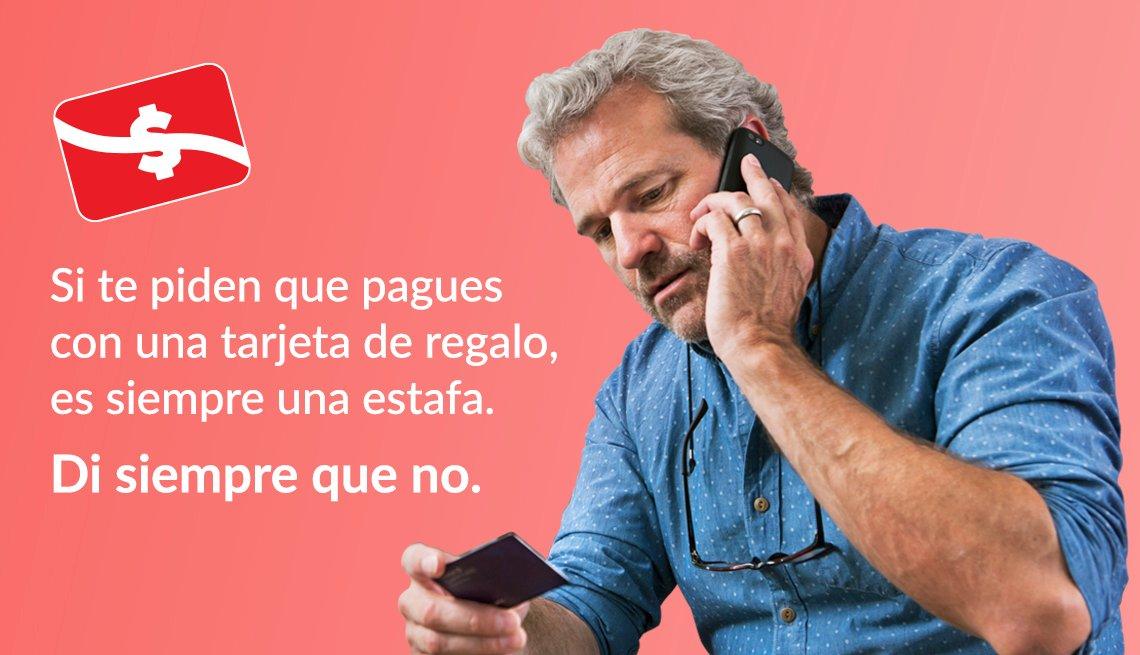 Hombre habla por teléfono y sostiene una tarjeta en su mano y al lado un letrero que dice si te piden que pagues con una tarjeta de regalo, es siempre una estafa. Di siempre que no.