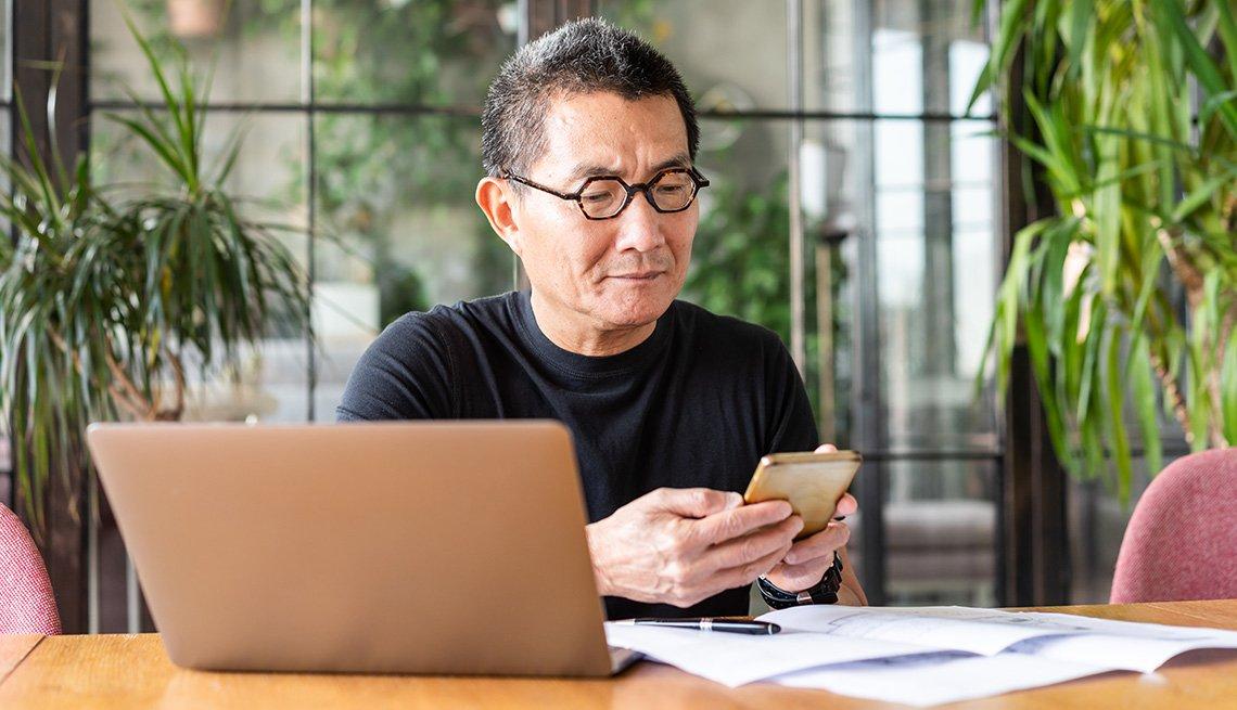Hombre mayor mira su teléfono móvil mientras está sentado en su oficina en casa.