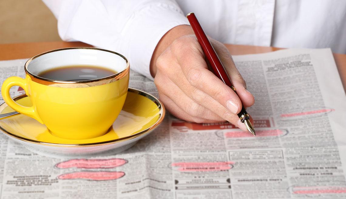 Persona señalando anuncios de trabajo de un periódico con un lapicero y una taza de café al lado