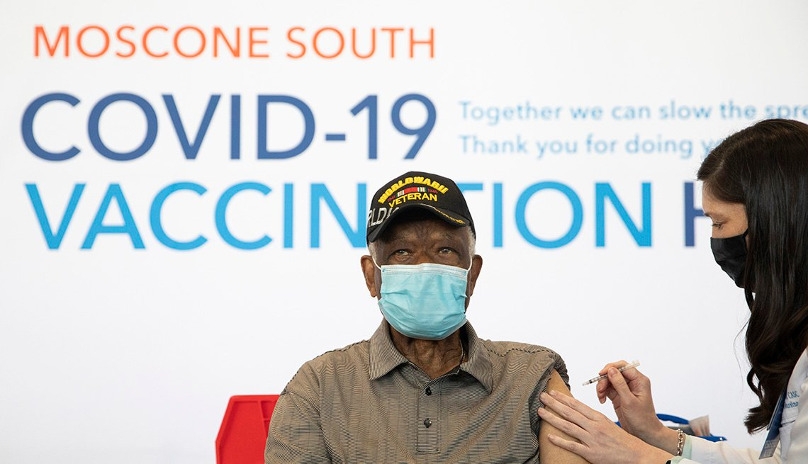 Ezekiel Logan, a 96-year-old World War II veteran, receives his first dose of the Pfizer COVID-19 vaccine