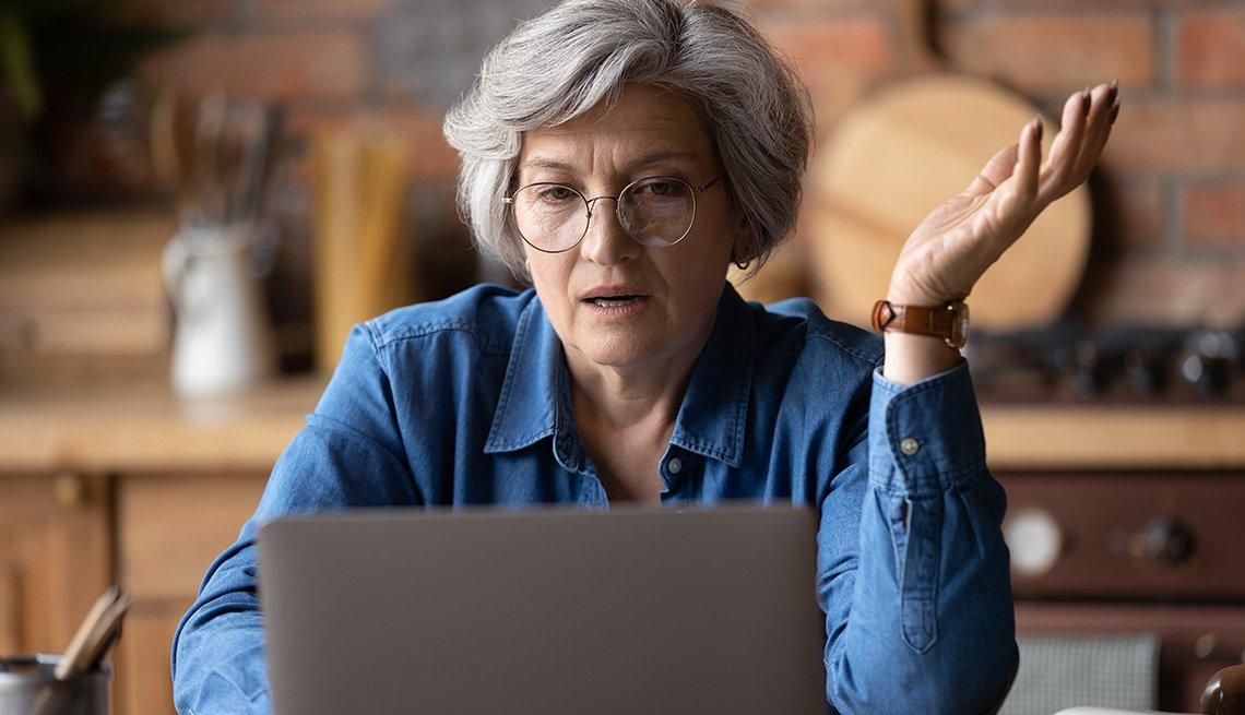 Mujer con gafas sentada frente a su computadora en la cocina de su casa