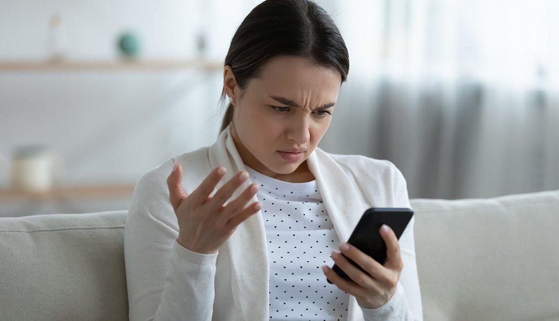 Mujer sentada en la sala de su casa y mirando el teléfono con expresión de angustia