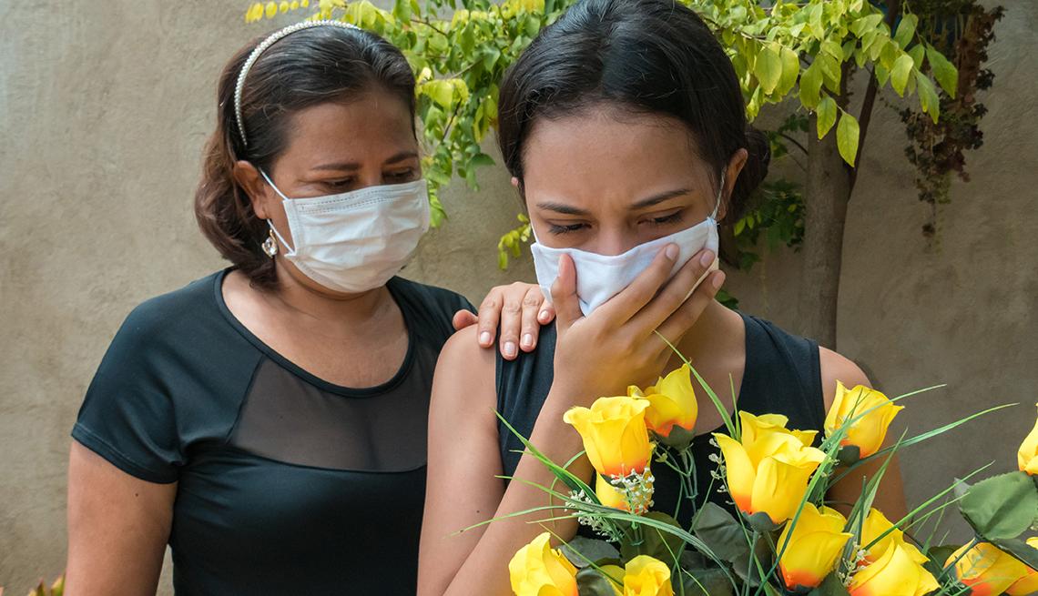 Dos mujeres de luto por la muerte de un familiar, una sostiene flores amarillas.