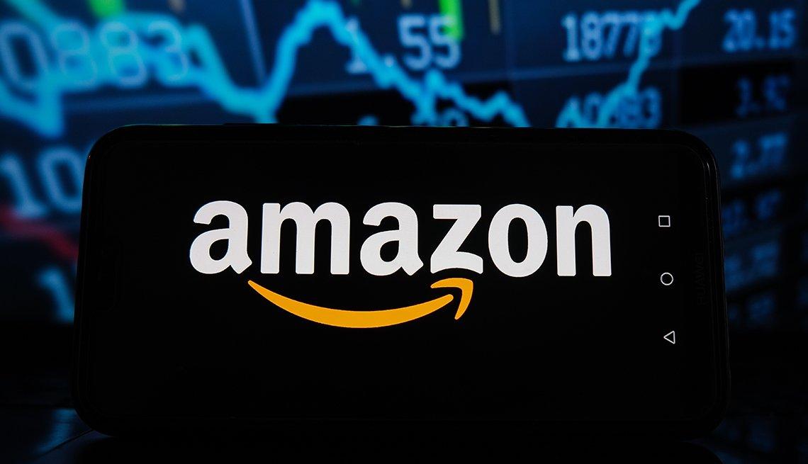Logo de Amazon que se ve en la pantalla de un teléfono y delante de una gráfica estadística de inversiones.